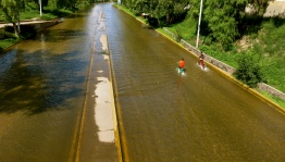 two children ride through what used to be a main avenue in San Luis Potosí city until it got flooded some years ago.