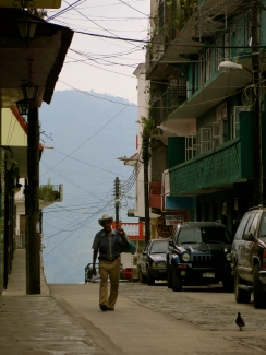 a bowlegged man strolls through the streets of Xilitla, San Luis Potosí