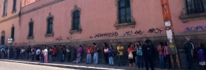 people line up on a main avenue in San Luis Potosí for a bus.