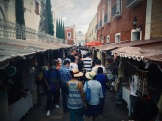 A mother and daughter shop the sunday market with matching hats while a wannabe hard gangster is concerned about his health in public. Atlixco, Puebla