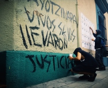 """protesters paste the faces of the missing students of Ayotzinapa and write a message to their government: """"Ayotzinapa, you took them alive [bring them back alive], justice"""". Oaxaca, Oaxaca"""