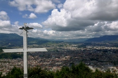 a cross watches over a city of shadows cast upon it, Quetzaltenango, Guatemala