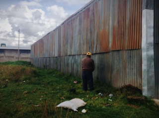 A Queztaltenango local pees on a wall in what he believes is peace, not realizing a tourist is taking his photo with the intention to upload it to the world wide web where potentially anybody with an internet connection can witness his personal doings, Guatemala