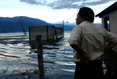 a local indigenous man looks out on what used to be part of his neighborhood, Lago Atitlan, Guatemala