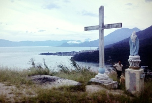 a man, his dog, his icon, the symbol of his religion, an ancient sacred patch of ceremonial earth of his Mayan ancestors, his lake, his town and his gringo tourist friend with a camera, Lago Atitlan, Guatemala