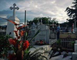 a child pays respects to a family member's grave in a cemetery in Estelí, Nicaragua on el Día de los Muertos