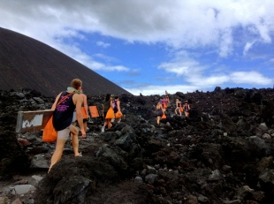 a group of white people carrying orange bags are climbing a volcano in Nicaragua