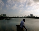A man walks with his head down while Cartagena slowly and steadily grows beside him.