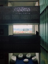 A man looks out onto the mountains surrounding Bogotá while talking on a cellular device on top of a futuristic empty living room.
