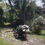 A plastic wares delivery boy packs his bike to the limit, Ecoaldea Feliz, Cundinamarca
