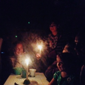 A few residents of the ecovillage enjoy the exclusive comfort of the cozy kitchen during a rainy night with no electricity, Ecoaldea Feliz, Cundinamarca
