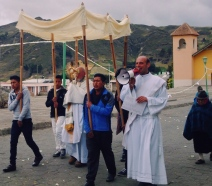 In a small, almost entirely Quechua village in the high sierras of Ecuador, a group of indigenous carry a fancy mobile awning for a church official while another religious official barks verses through a megaphone from scriptures. the listener's ancestors were forced into following, continuing to save this latest generation from their barbaric hell-bound ways. Zumbahua