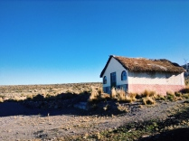 Electrical towers hide behind a simple and humble home in the high plains of peru, providing electricity for the basic necessity of a television in which to watch dramatic telenovelas from Mexico. Colca Canyon