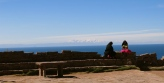 Two indigenous women chat in the early morning sun while the tall peaks of Bolivia loom in the distance. Lake Titicaca