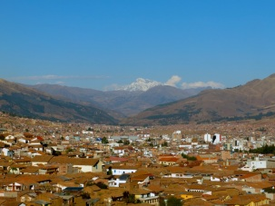 A snow capped peak keeps watch on Cusco down below.