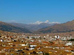 A snow capped peak keeps watch on Cusco down below.