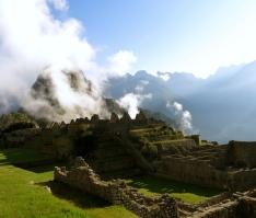 Wainu Picchu timidly hides behind a layer of mist. Machu Picchu